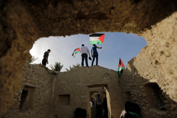 Activists hold Palestinian flags as they walk through the old village of Ein Hajla near Jericho on Jan 31, 2014 [Reuters]