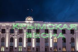 At night, the words (***)Crimean Spring(***) are projected onto a government building in Simferopol(***)s Lenin Square prior to a victory party amid exit polls suggesting at least 90 percent voted in favour of joining Russia.