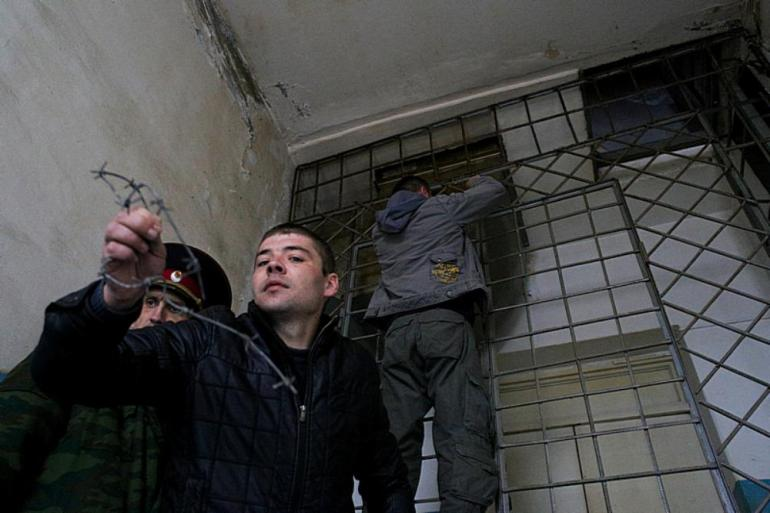 Members of the Crimean force unblock steel grating.