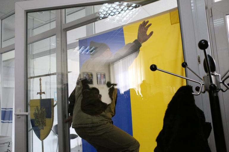 A man tries to take off the Ukranian flag. The man originally aimed to burn the flag, but was stopped by plains-clothed people.