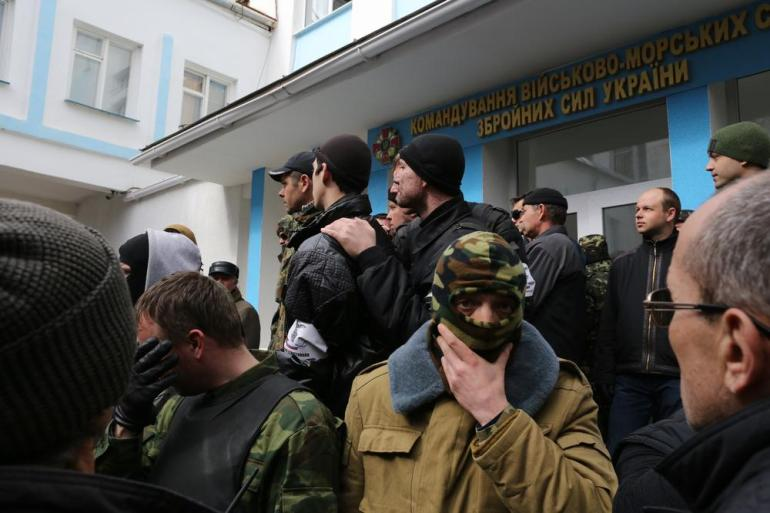 "A member of Crimean ""self-defence"" force puts on a mask before being photographed. The force blocked entrances to the main building of Ukranian navy headquarters."