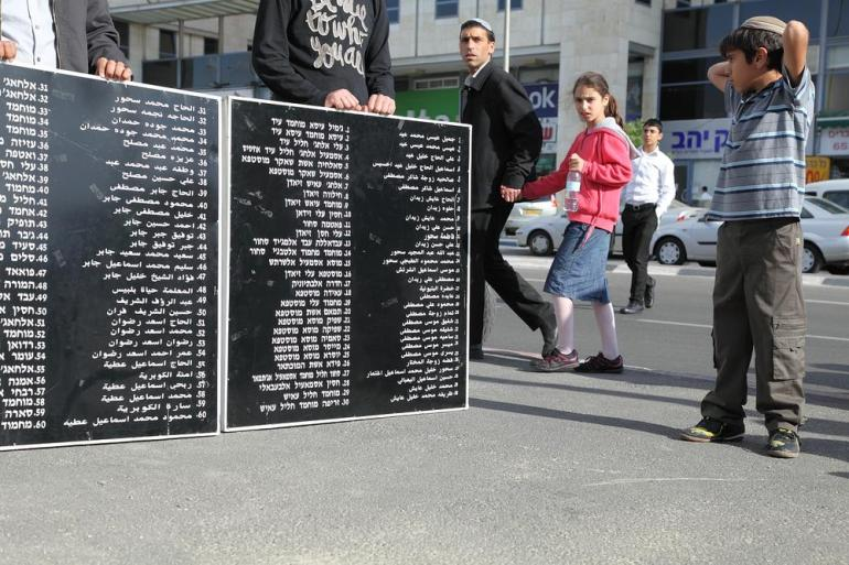 Activists carried the names of the more than 100 Palestinians who were killed in Deir Yassin.