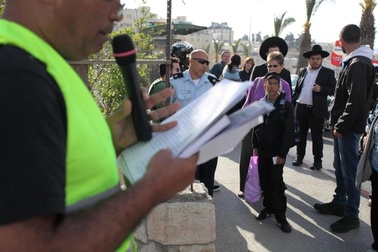 As the names of 38 members of the Radwan family, who were killed during the massacre, are read out, two Orthodox Jewish Israelis pause briefly to listen.