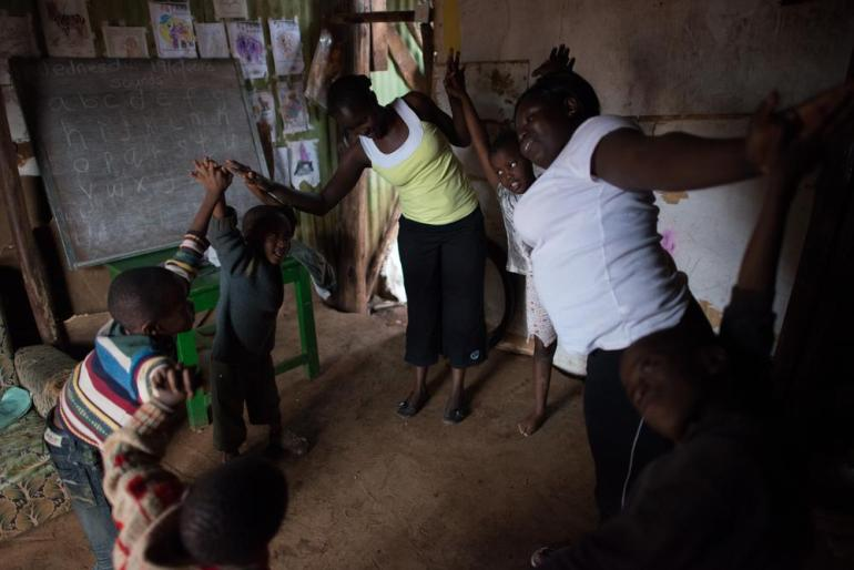 Atieno and her assistant Susan Njeri, 23, teaching a yoga class at a small school in Kibera. Students practice a selection of standing poses, stretching and games.