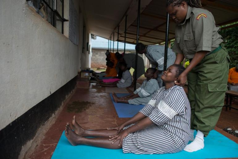 "A guard massages a prisoner during a yoga class in Langata Women(***)s Prison. The prisoners attending the class are not necessarily guilty, some are awaiting trial. Sharon, a prisoner, said: ""When I do it, I don(***)t feel neglected but I feel loved."""