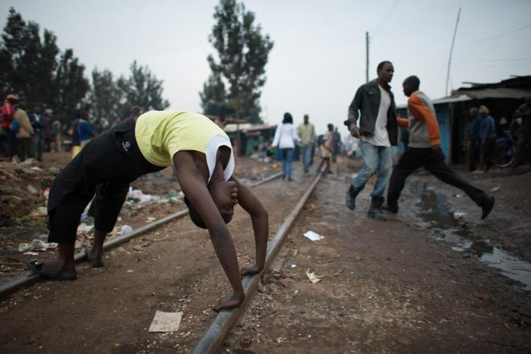 Susan Njeri, 23, practices the Wheel Pose on the railway line at the entrance of Kibera.