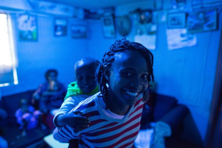 Nicole Akoth, 21, and her 3-year-old son Alex stand in her parents(***) home in Kariobangi, Nairobi. Nicole has been practising yoga for two years and eventually wants to open her own art school and yoga centre.
