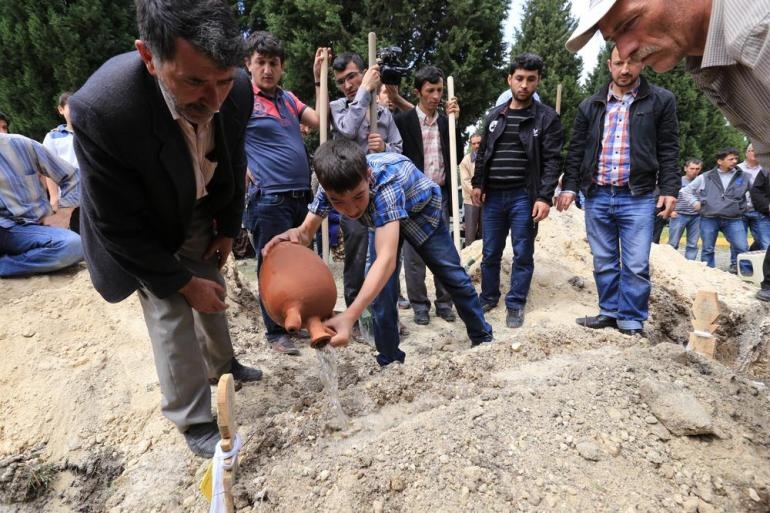 Enes Ilci is pouring water over his father(***)s grave.