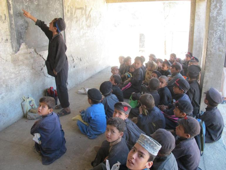 Students have to sit on the ground in classes since the furniture destroyed in the attacks have yet not been replaced.