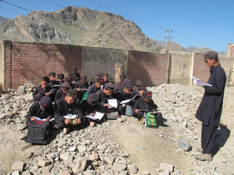 A senior student teaches his juniors as they sit among the debris of a destroyed school.