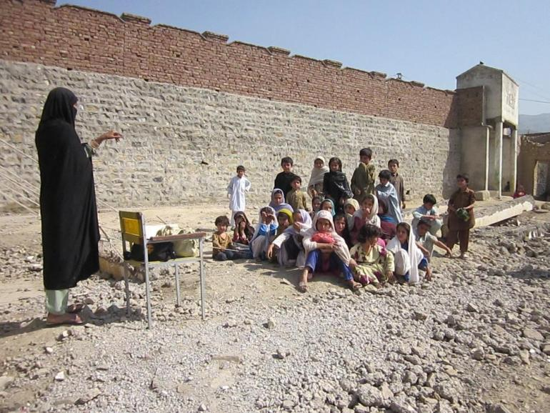 A female teacher in the Jamrud subdivision gives lessons in the open air.