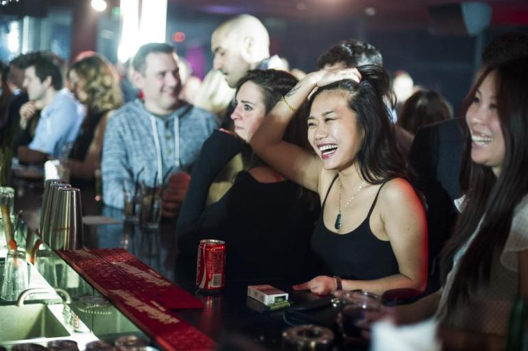 Two young women laugh as they wait at the bar at Ladies(***) Night at Bar Rouge in the historic Bund 18. Bar Rouge is one of the stalwarts of the city(***)s high-end bar scene.