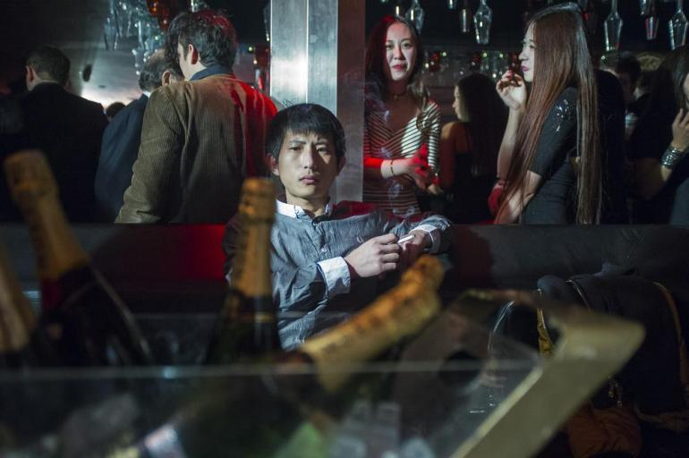 A young man smokes a cigarette while he waits for his friends to arrive at a table with a dozen bottles of champagne, at Bar Rouge in the historic Bund 18 building. Bar Rouge will celebrate its 10-year anniversary in 2014.