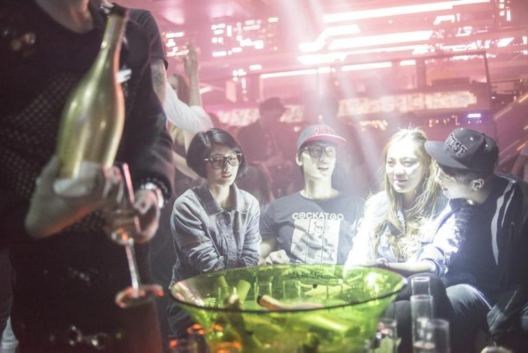 Young clubbers are served Bottega Gold prosecco, a high-end sparkling wine, at a table at Linx.