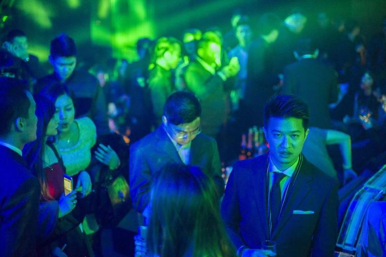 A man dressed in a suit and tie stands with a glass of champagne amid the crowd at Linx during its soft opening.
