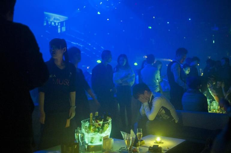 A man sits at a table in front of a clear, illuminated bucket containing empty and unopened bottles of champagne at M2, one of the city(***)s most popular nightclubs. The club mainly attracts Chinese patrons rather than Western expatriates.