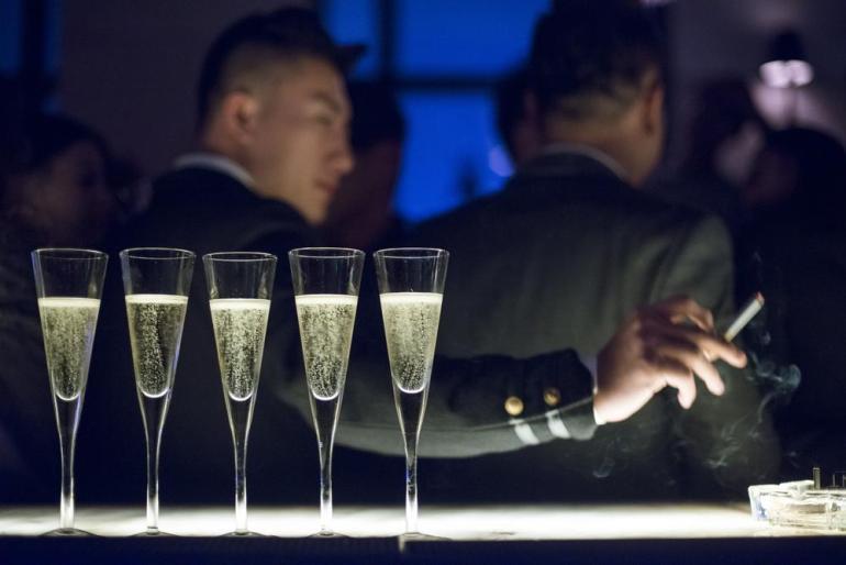 A man smokes at a bar lined with glasses of champagne during the cocktail reception at the Black Swan party at M1NT, one of Shanghai(***)s most exclusive nightclubs.