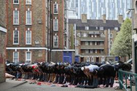 Muslims attend Friday prayers in the courtyard of a housing compound in east London [Reuters]