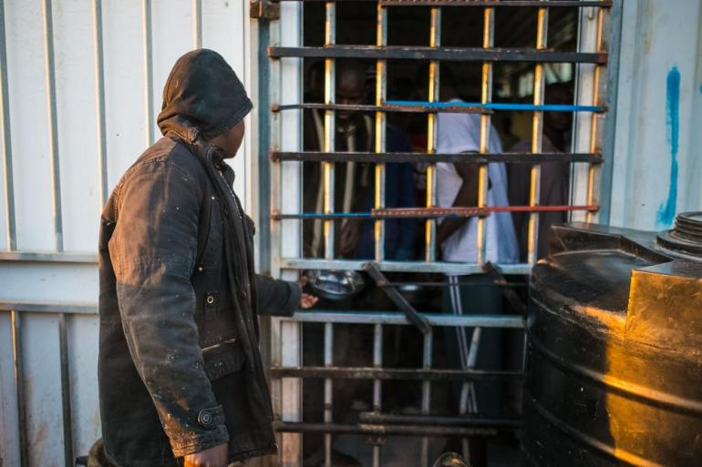 The prisoners drink water and eat out of metal bowls. Water is kept right outside the bars in large containers.