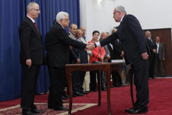 Palestinian President Mahmoud Abbas and the new unity government Prime Minister Rami Hamdallah with Foreign Minister Riyad al-Malki during the swearing-in ceremony of the government [EPA]