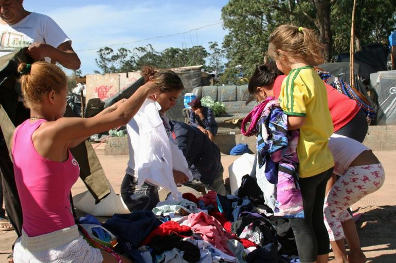 The camp relies entirely on donated food and clothing. A group of women and children sort through discarded clothes and shoes for new items.