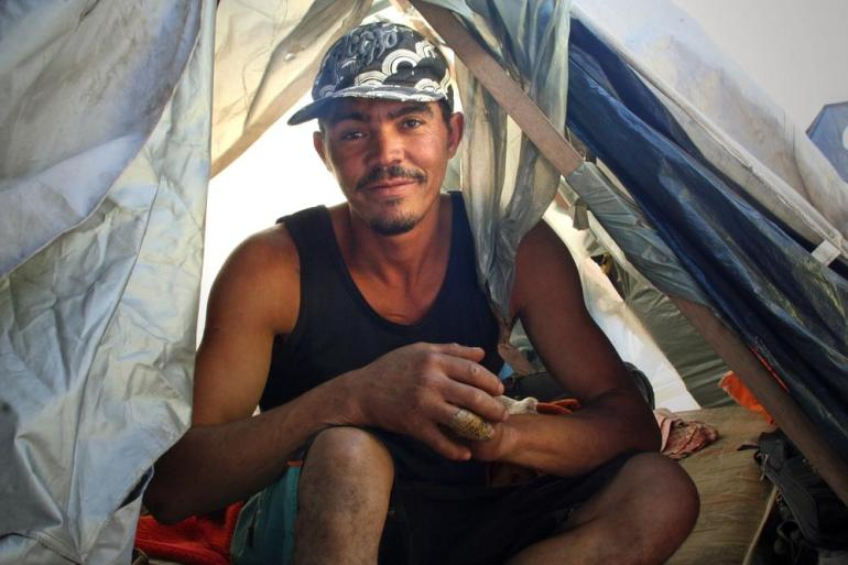 Claudio Lessa Souza, 31, was eager to show journalists how little he had inside his tent: shoes, a mattress, and a blanket.