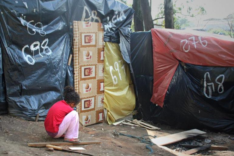 A small girl plays outside the door of her family(***)s tent near the kitchen and gathering area.