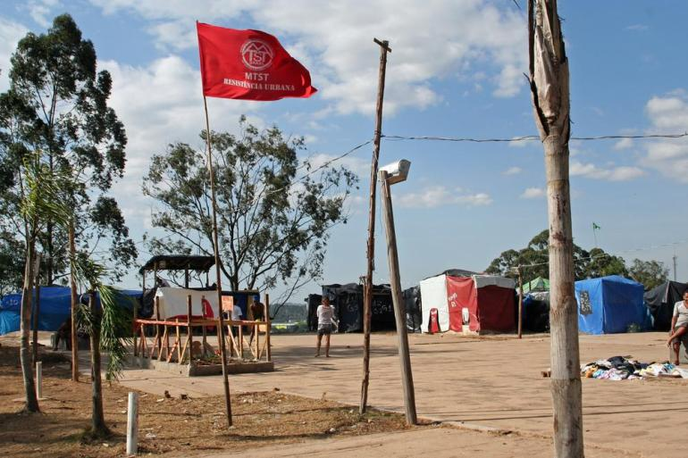 A red Homeless Workers Movement flag flies at the camp. The organisation is one of the most contentious groups the government has had to deal with ahead of the World Cup.