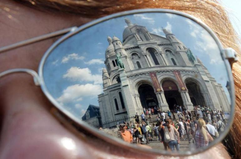 Sunglasses reflect the Sacre Coeur basilica in Paris, France.