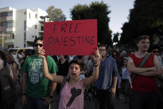 Israeli activists carry placards during a protest against the war on the Gaza strip, in Tel Aviv on July 9 [AFP]