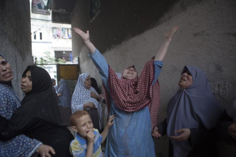 Palestinian women react during the funeral of the three children.