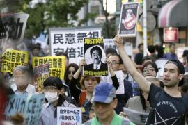Japanese citizens have protested against a defence policy change by Prime Minister Shinzo Abe [EPA]