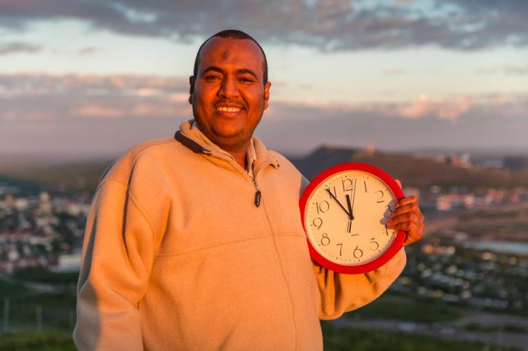 Idris Abdulwhab displays the time - 5 minutes before midnight - while the sun remains bright.