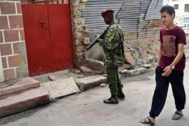 A young resident walks past an armed police officer at the scene of an attack on three Russian nationals, one of whom died, in Mombasa's old-town district in July [AFP]
