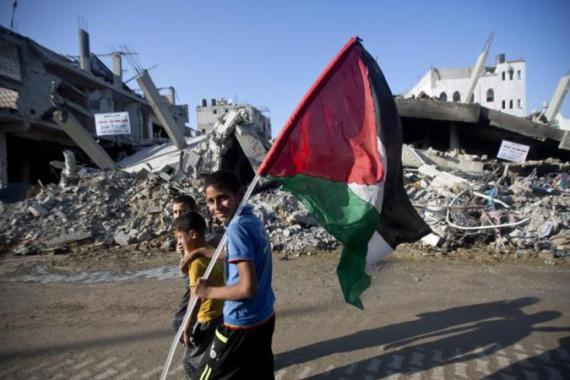 A group of Palestinian boys, one carrying the national flag, walk past destroyed houses in the Shejaiya neighborhood of Gaza City [AFP]
