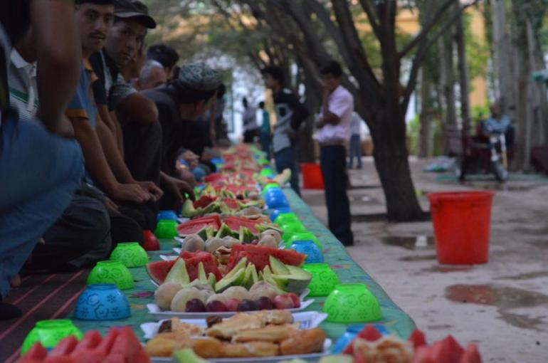 Believers wait by plates of fruit inside the Id Kah Mosque for the breaking of the fast.