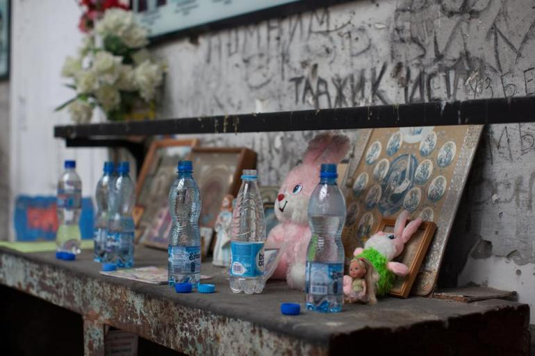 People bring bottles of water, flowers and toys to commemorate the children who died during the siege. [Andrei Kovalenko/Al Jazeera]