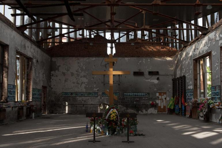 The walls of the gym are covered with handwritten verses and poems. A large wooden Orthodox cross is in the middle of the hall. [Andrei Kovalenko/Al Jazeera]