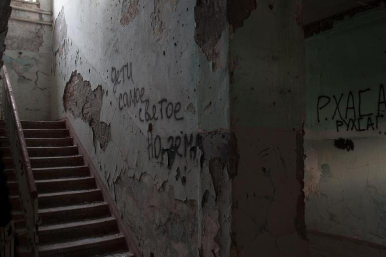 Despite the ban on walking through the building's ruins, notes in memory of the dead are scribbled on the walls of the school.