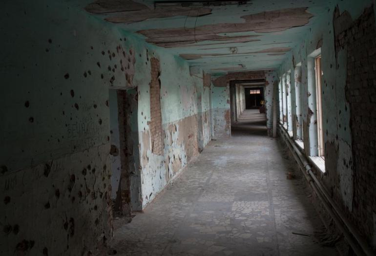 The school's empty corridors are riddled with bullet holes. [Andrei Kovalenko/Al Jazeera]