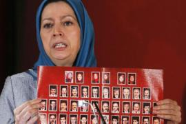 Maryam Rajavi, president-elect of the National Council of Resistance of Iran, shows a banner with pictures of Iranian dissidents killed in Camp Ashraf in Iraq [Reuters]