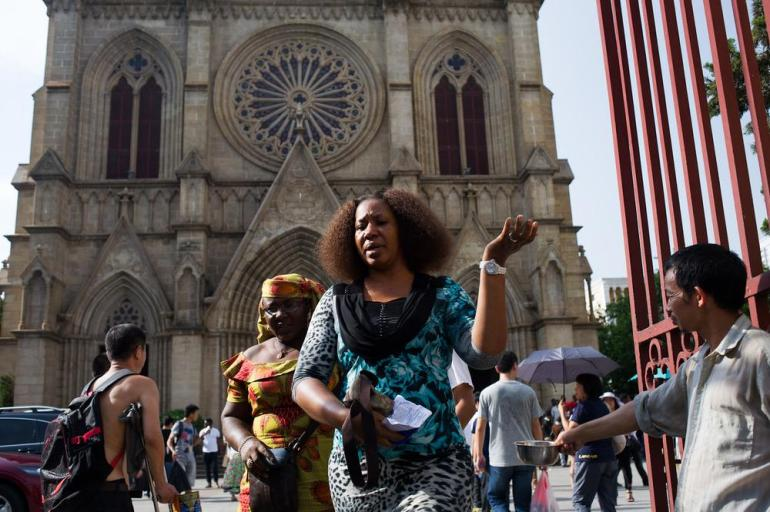 Two female African worshippers walk by a throng of beggars as they leave the Sacred Heart of Jesus Cathedral after Sunday service. Guangzhou has the largest African community in Asia and the church(***)s English language Sunday service attracts more than 1,000 African Christians each week.