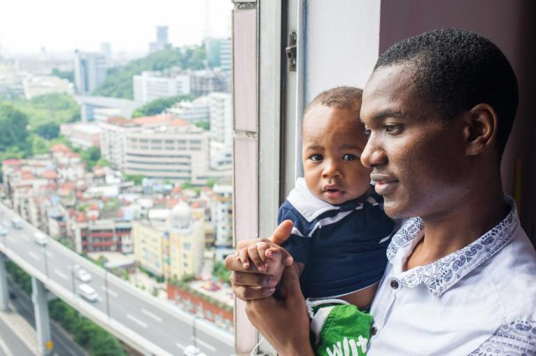 Bah Umaru Alpha, 26, from Kenema, Sierra Leone, and his nine-month-old son Mohammed, at the window of Alpha(***)s apartment in the Tianxiu Building near Xiaobei metro station.