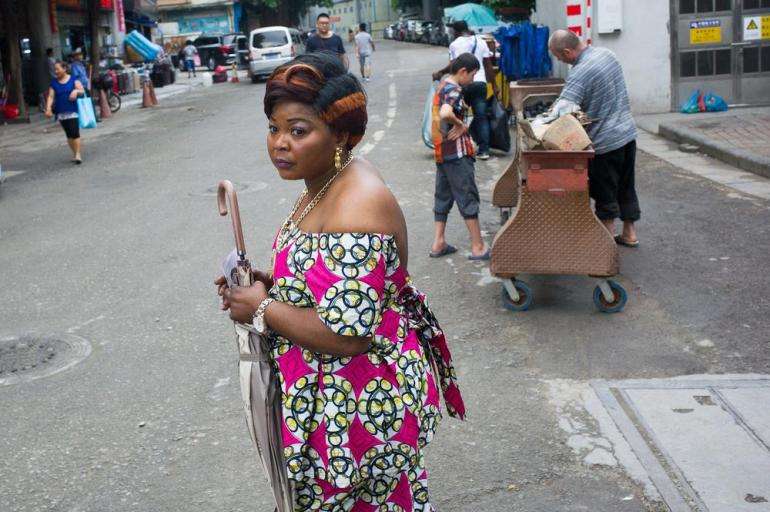 An African woman crosses a road near a wholesale market near Xiaobei metro station while an ethnic Uighur from Xinjiang Province sells kebabs from a grill by the roadside.
