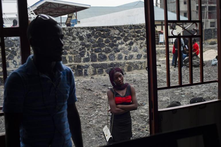 A Congolese adolescent watches a music rehearsal in a shipping container that has been converted into a practice room at the Maison des jeunes, a cultural youth centre in Goma.