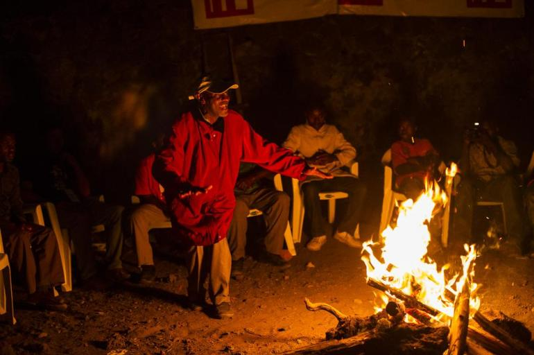 A respected poet from Goma leads a session around a bonfire, exchanging poems and jokes, during the SKIFF festival. The festival melded local and Western styles, incorporating traditional aspects of culture.