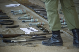A soldier stands near weapons seized from police and displayed at a barracks in the capital Maseru [AFP]