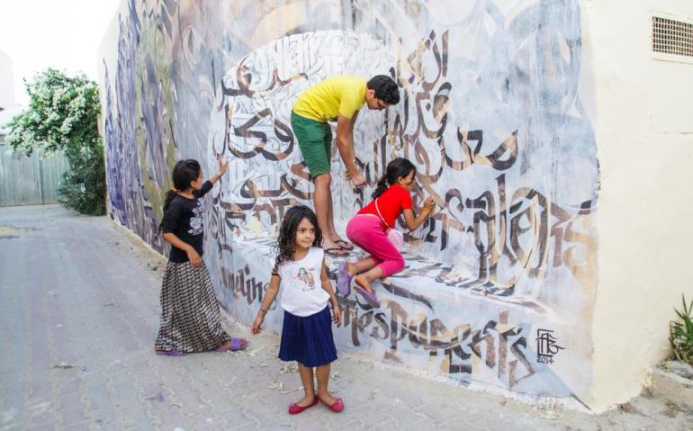 Children clamber around this blend of English and Arabic calligraphy.