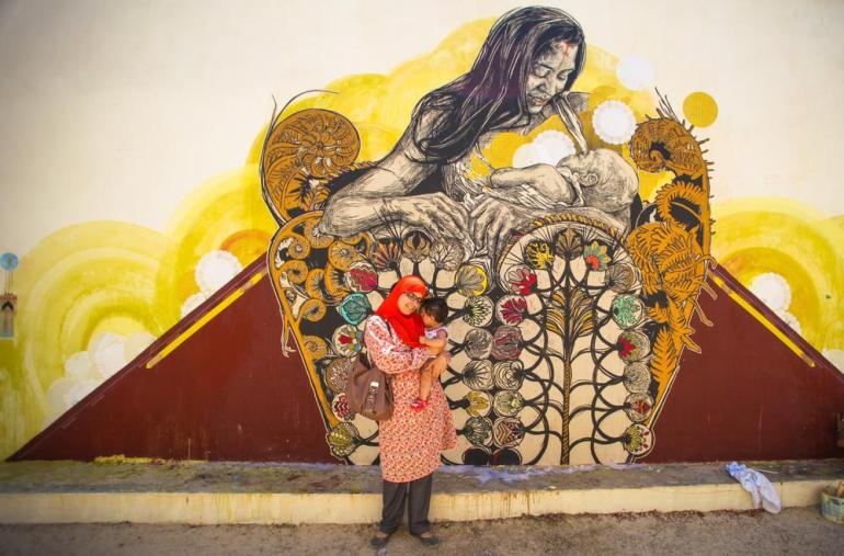 A woman and child stand in front of a universal image of maternal love.