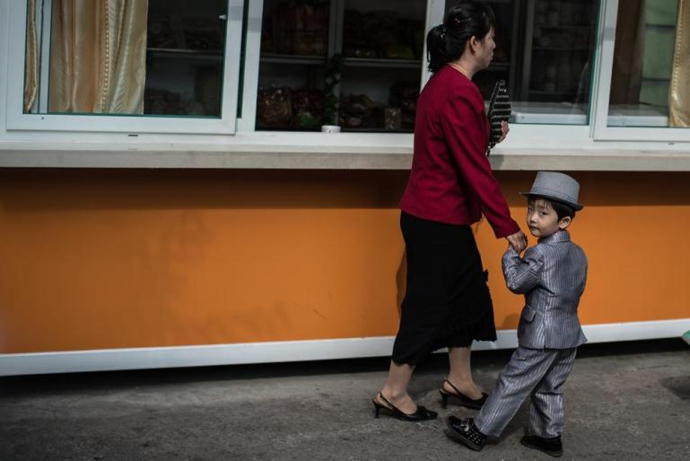 A mother and her child on a street of Pyongyang. [Miguel Toran/Al Jazeera]